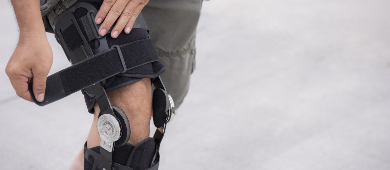close up of a man tightening his knee brace