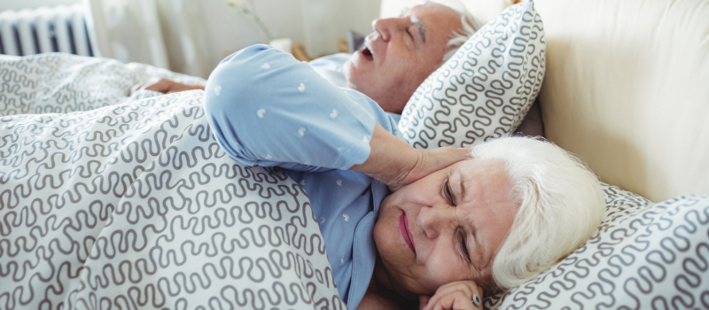 Older woman holding her hears while sleeping next to her snoring husband